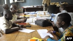 Guinean election officials examine votes at a collation center in the Conakry neighborhood of Ratoma, Oct. 14, 2015. Turnout in Sunday's controversial first round of balloting was estimated at almost 75 percent.