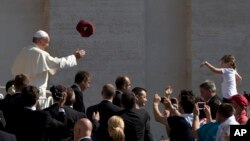 A worshipper tosses a hat into the air as Pope Francis arrives for his weekly general audience in St. Peter's Square, at the Vatican, in Rome, June 10, 2015.