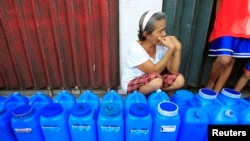 FILE - A resident queues with plastic containers to collect drinking water in Rosario.