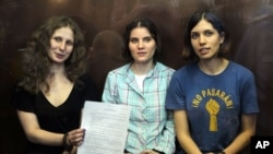3 thành viên ban nhạc Pussy Riot ngồi trong phòng kiếng tại một tòa án ở Moscow 17/8/1012. Từ trái: Maria Alekhina, Yekaterina Samutsevich và Nadezhda Tolokonnikova