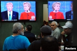 FILE -- People watch the first U.S. presidential debate in a restaurant, Sept. 26, 2016, in the Queens borough of New York City.