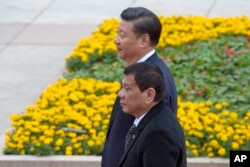 FILE - Philippine President Rodrigo Duterte, front, walks with Chinese President Xi Jinping during a welcome ceremony outside the Great Hall of the People in Beijing, China, Oct. 20, 2016.