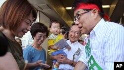 29일 전직 총무상 마스다 히로야 도쿄도지사 후보가 유권자들과 악수하고 있다.