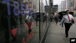 Seorang pria berjalan di dekat layar yang menunjukkan indeks saham di Hong Kong Stock Exchange. Saham-saham Hong Kong mengalami penurunan terbesar selama 6 bulan terakhir Kamis (11/2).