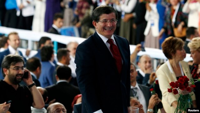 Turkey's Foreign Minister Ahmet Davutoglu greets supporters during a meeting of the ruling AK Party (AKP), in Ankara, August 27, 2014.