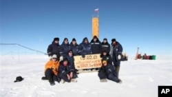 """Russian researchers at the Vostok station in Antarctica after reaching subglacial Lake Vostok. Scientists hold a sign reading """"05.02.12, Vostok station, boreshaft 5gr, lake at depth 3769.3 metres."""""""