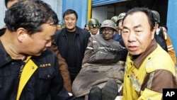 Rescuers carry a survivor out of the Qianqiu coal mine after a rock burst accident in Sanmenxia, Henan province, China, November 4, 2011.