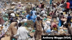 South Sudanese pick through a sea of trash outside Juba, looking for plastic bottles that they can exchange for money at a local NGO.