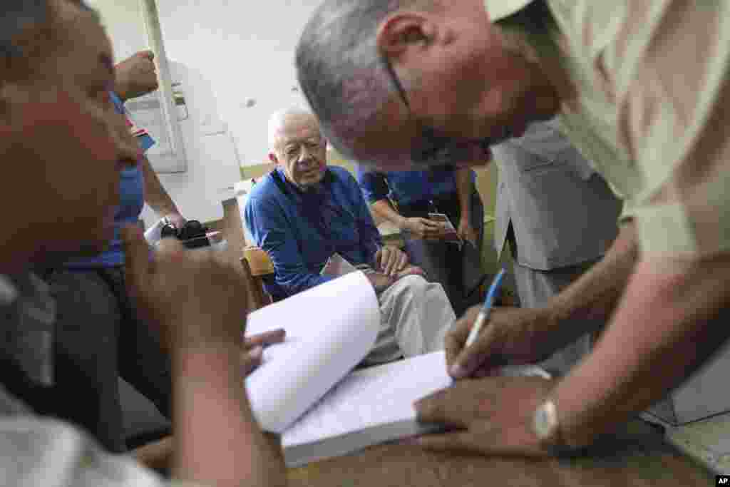 Former U.S. President Jimmy Carter, center, observes the election process inside a polling station in the Sayeda Aisha neighborhood of Cairo, Egypt, Wednesday, May 23, 2012. The Carter Center is in Egypt to monitor the presidential elections.