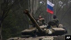 Separatis pro-Rusia menaiki tank dengan bendera Rusia di Donetsk, Ukraina timur (21/7). AS dan Eropa menuduh Rusia membantu pemberontak di Ukraina timur.