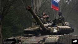 Pemberontak pro-Rusia mengendarai tank berbendera Rusia di sebuah jalan di Donetsk, Ukraina timur (21/7). (AP/Vadim Ghirda)