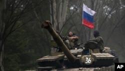 Phiến quân thân Nga trên một chiếc xe tăng có treo cờ Nga.