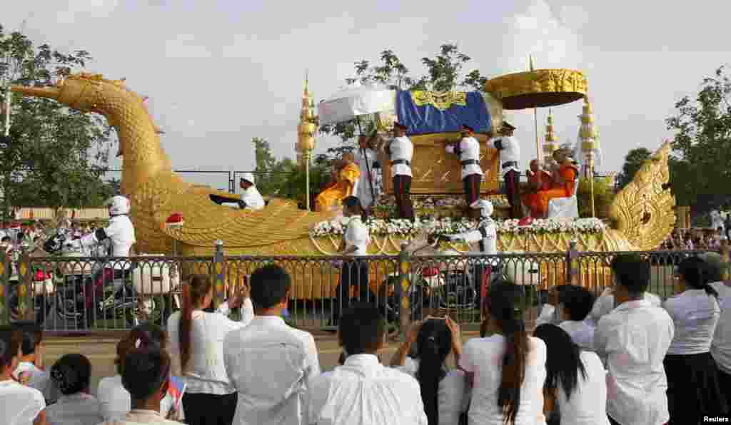 People pray as they see the coffin of former king Norodom Sihanouk on a royal truck along a street in Phnom Penh October 17, 2012.