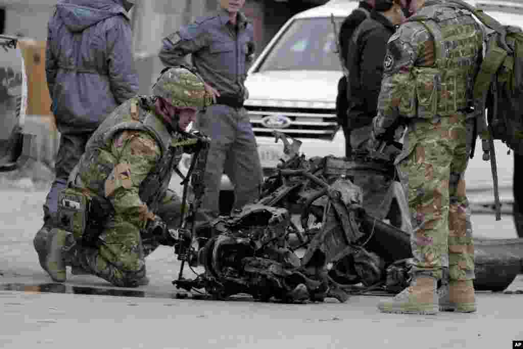 U.S. forces examine the remains of a car after a suicide car bomb attack on the Jalalabad-Kabul road in Kabul, Afghanistan, Dec. 27, 2013.