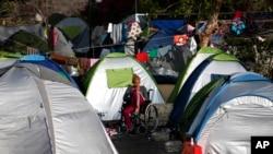 Une réfugiée au milieu des tentes dans un camp à Athènes, 9 avril 2016.