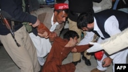 Cư dân Pakistan an ủi một cậu bé bị mất các thành viên trong gia đình sau vụ nổ bom ở tây bắc Pakistan, ngày 27/2/2012