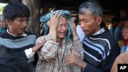 Villagers try to comfort a weeping woman, a relative of Khin Win, who was fatally shot Tuesday during a confrontation with a police and mine security guards at Letpadaung copper mine.