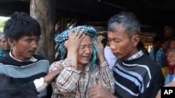 Dân làng an ủi thân nhân của một nạn nhân bị bắn chết trong vụ đối đầu với cảnh sát và nhân viên bảo vệ mỏ đồng Letpadaung Taung.