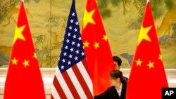 Tư liệu- Ảnh chụp ngày 14/2/2019. Nhân viên TQ điều chỉnh quốc kỳ Mỹ và Trung Quốc trước phiên khai mạc cuộc đàm phán giữa đại diện thương mại của hai bên. (AP Photo/Mark Schiefelbein)