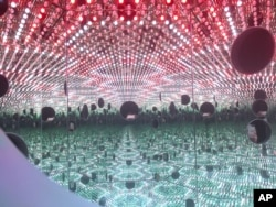 "Colored lights appear in the Infinity Mirror Room created by Japanese artist Yayoi Kusama, part of the exhibit, ""Yayoi Kusama: Festival of Life,"" on display at the David Zwirner gallery in the Chelsea section of New York, Nov. 21, 2017."