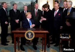 President Donald Trump, surrounded by business leaders and administration officials, gives the pen to Lockheed Martin CEO Marillyn Hewson after signing a memorandum on intellectual property tariffs on high-tech goods from China, at the White House.