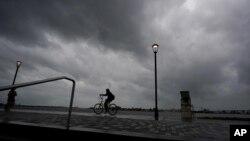 Ida Kasırgası karaya vurmadan önce New Orleans'ta Mississippi Nehri kenarında bisiklete binen bir kişi.