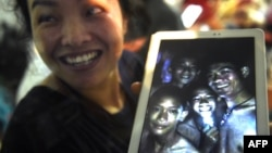 A happy family member shows a picture of the missing boys. (AFP PHOTO)