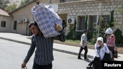 Syrian refugees walk with their belongings on the Lebanese-Syrian border, in al-Masnaa, July 20, 2012