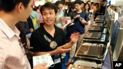 FILE - An exhibitor details the latest specifications of his laptop computers to a visitor during a computer trade show in Taipei, Taiwan.
