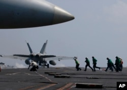 FILE - A U.S. Navy F-18 fighter jet takes off from the deck of the USS Carl Vinson (CVN 70) aircraft carrier following a routine patrol off the disputed South China Sea, March 3, 2017.