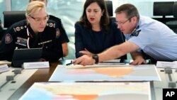 Queensland Fire and Emergency Services Commissioner, Katarina Carroll, from left, Queensland Premier Annastacia Palaszczuk and Queensland Police Deputy Commissioner Bob Gee discuss the approaching cyclone at the Emergency Services Complex in Brisbane, March 19, 2019.