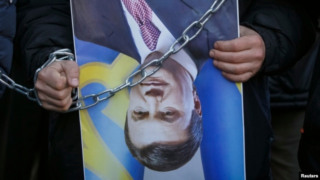 FILE - A protester holds an upturned poster of Ukrainian President Viktor Yanukovych during a rally in Kyiv, Dec. 26, 2013.