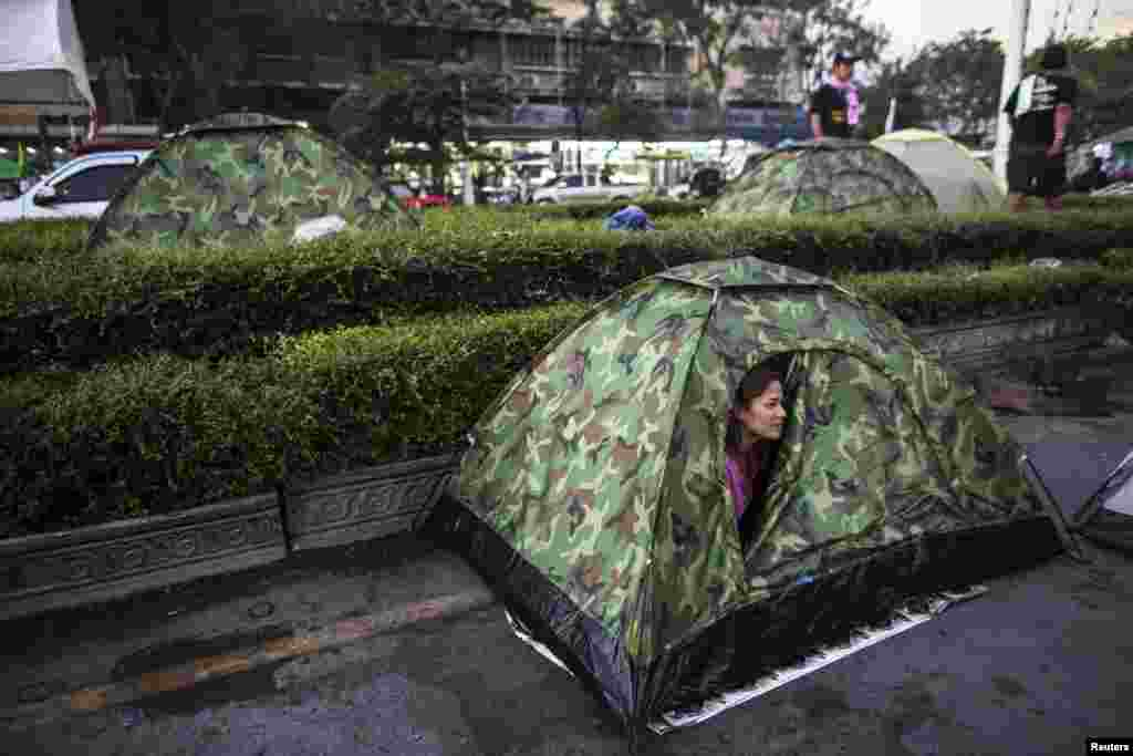 A woman looks out of her tent after waking up in the anti-government protester encampment near the Democracy Monument, Bangkok, Thailand, Jan. 12, 2014.