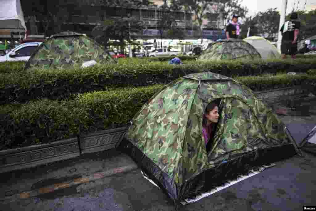 Một phụ nữ quan sát bên ngoài từ căn lều của mình tại khu trại của người biểu tình chống chính phủ, gần Tượng đài Dân chủ ở Bangkok, Thái Lan 12/1/14.