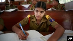 In this Friday Aug. 8, 2014 photo, a student writes notes inside a classroom at a Sainik School in the northeastern Indian state of Assam.
