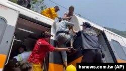 Tangkapan layar dari video yang dirilis oleh hasnews.com.tw, tampak seorang penumpang (tengah) sedang dibantu naik ke atas kereta yang anjlok di terowongan Hualien, di bagian timur Taiwan, Jumat, 12 April 2021. (Foto: hsnews.com.tw via AP)