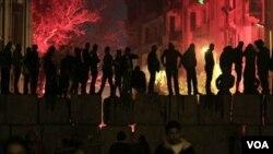 Para demonstran yang marah atas kerusuhan sepakbola melempar kembang api dalam protes di dekat Lapangan Tahrir, Kairo (3/2).