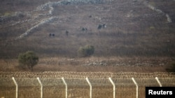 Rebel fighters are seen in Syria near the border fence with the Israeli-occupied Golan Heights, Sept. 2, 2014.