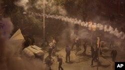 Manifestantes se alejan del gas lacrimógeno arrojado por la policía nacional durante enfrentamientos en Barcelona. (AP)