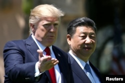 FILE - U.S. President Donald Trump and China's President Xi Jinping chat as they walk along the front patio of the Mar-a-Lago estate after a bilateral meeting in Palm Beach, Florida, April 7, 2017.