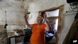 Seorang warga menunjukkan rumahnya yang rusak akibat pertempuran di Donetsk, Ukraina timur (14/8).