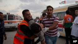 اسرائیلی فوج کی گولی کا نشانہ بننے والے ایک نوجوان کو فلسطینی عملہ لے جا رہا ہے۔ فائل فوٹو
