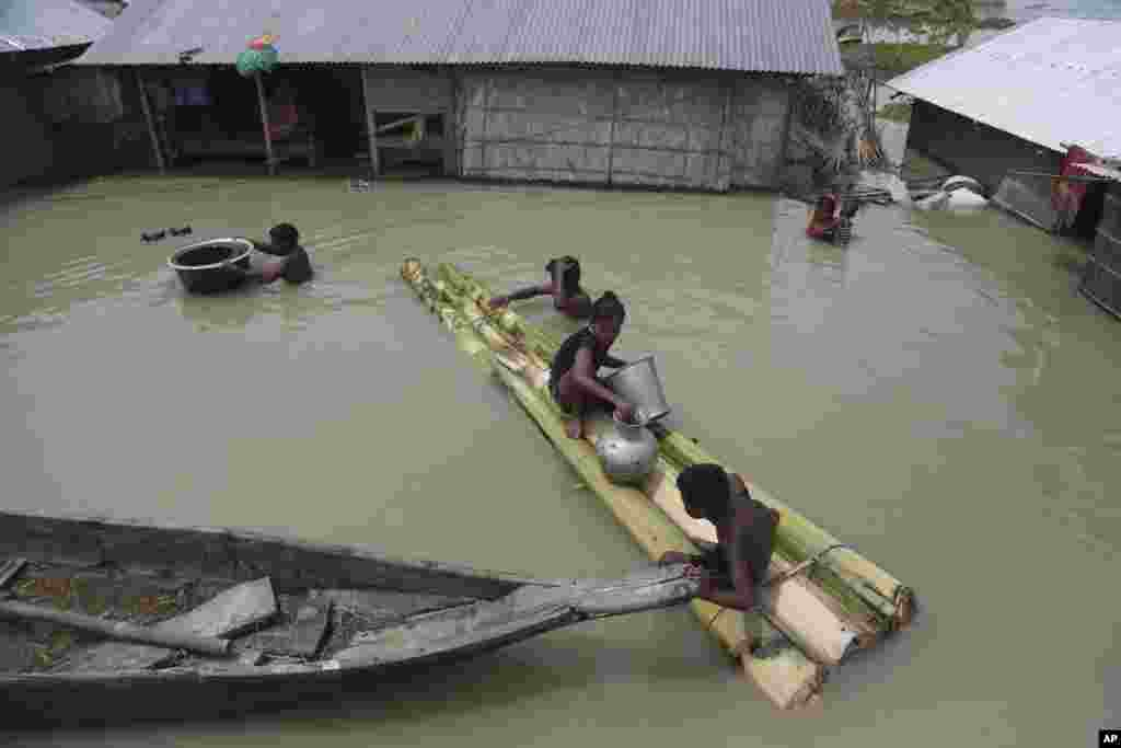 Flood-affected villagers are seen near their partly underwater houses in Gagolmari village, Morigaon district, Assam, India.