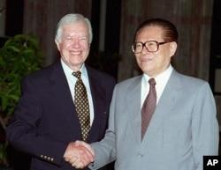 1997年7月24日,美国前总统吉米·卡特与中国国家主席江泽民在北戴河握手。