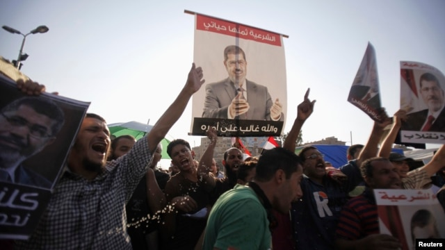 Members of the Muslim Brotherhood and supporters of deposed Egyptian President Mohamed Morsi shout slogans during a protest at Rabaa Adawiya Square, where they are camping, in Nasr City, east of Cairo, Aug. 7, 2013.
