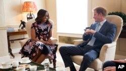 Foto resmi yang dirilis oleh Gedung Putih memperlihatkan Ibu Negara AS Michelle Obama berbincang-bincang dengan Pangeran Harry dalam upacara minum teh di Istana Kensington di tengah-tengah kunjungan Michelle Obama ke Inggris.
