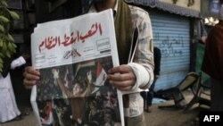 Египтянин читает газету на первой полосе которой - статья об отставке Мубарака.