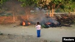 Người dân Miến Ðiện chụp hình các tử thi bị đốt cháy trong vụ bạo động ở Meikhtila, ngày 22/3/2013.