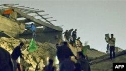 Sledbenici Moamera Gadafija ispituju štetu posle vazdušnog napada u Tripoliju na Gadafijev kompleks, 25. april 2011.