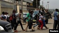 Des passants courent alors qu'il quitte le port d'Abidjan après avoir entendu des tirs, en Côte d'Ivoire, le 18 janvier 2017.